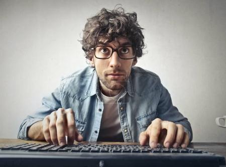 Mann mit Brille tippt auf Tastatur