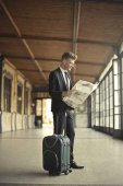 Young businessman with suitcase reading newspaper
