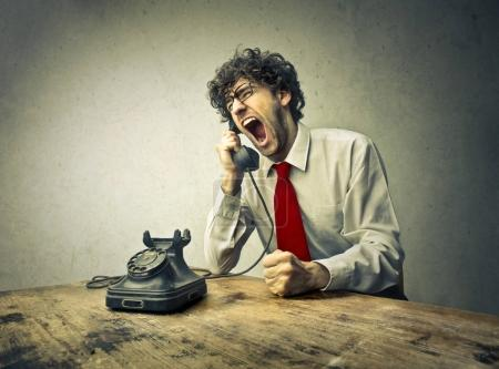 Businessman yelling while talking on retro phone...