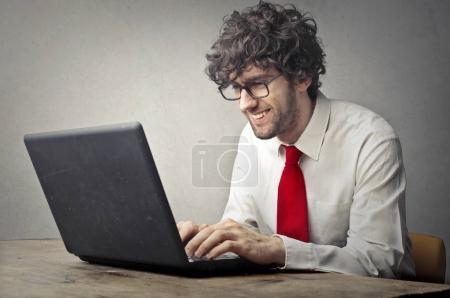Handsome businessman working on laptop inside