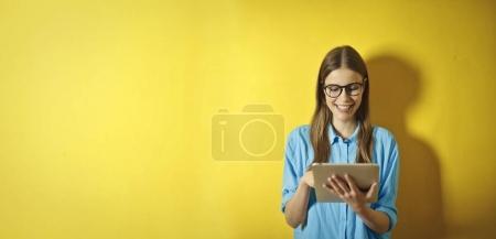 Photo pour Fille avec un comprimé sur un mur jaune - image libre de droit