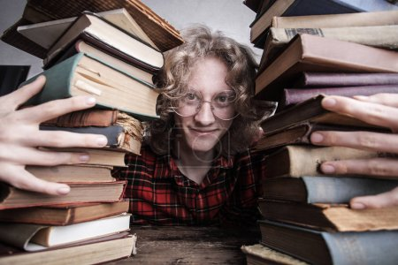 boy in the middle of two pile of books