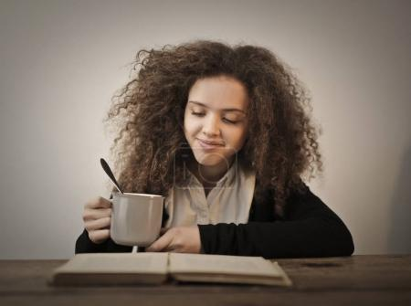 Girl drinking tea and reading