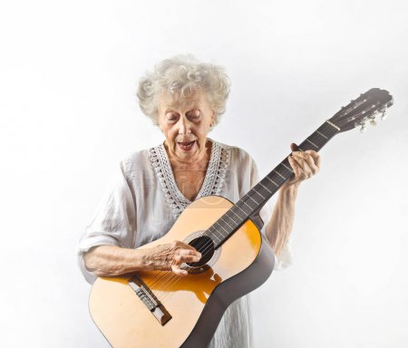 Aged woman playing acoustic guitar