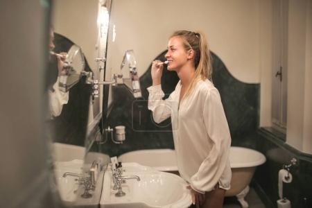 Girl brushing her teeth in an elegant bathroom