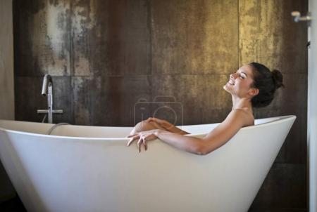 Caucasian young woman relaxing in a bath