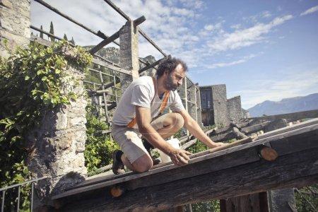 Artisan repairing a construction in a garden