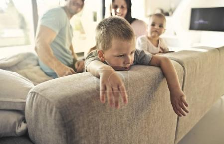 Sad child with a sad expression on a sofa with his family on background