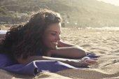 Beautiful smiling caucasian young woman sunbathing on the beach