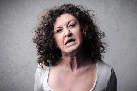 Portrait of a caucasian woman with curly hair with an angry face