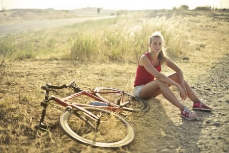 in the coutrysideBlonde girl resting alongside a red bicycle in the countryside