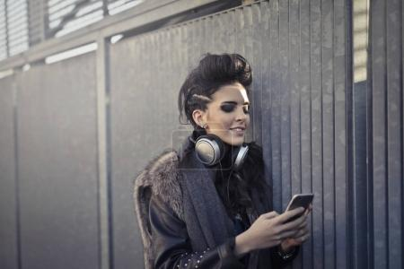 Young caucasian woman whith a grunge look using her smartphone