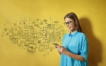 Portrait of a caucasian young woman with glasses and a blue shirt using her smartphone