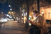 Buisnessman sitting on a bench and using his mobile phone in a city street at night
