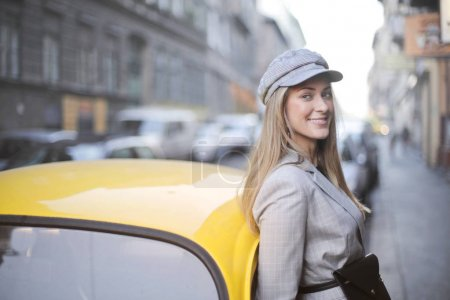 Elegant caucasian woman with a hat supported by a taxi on a city street