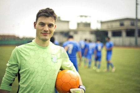 Caucasian young goalkeeper with a soccer ball on the football field