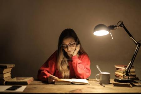 Caucasian student girl with glasses studying from a book on her desk
