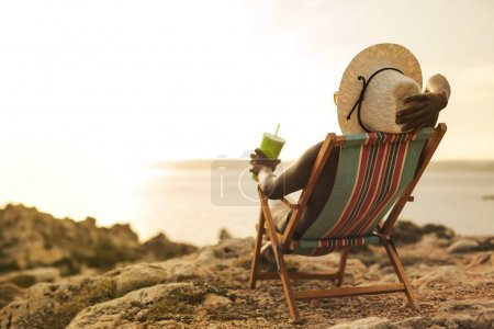 African girl with a hat and a drink in her hand sunbathing on a deckchair facing the sea
