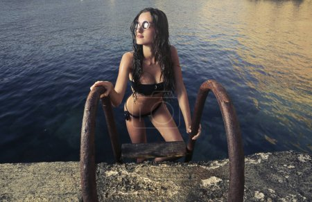 beautiful caucasian girl with sunglasses and a bikini coming out from the water