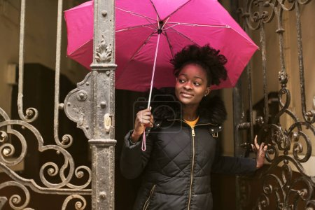 African woman going outside with a pink umbrella