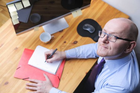 Buisnessman writing on a notebook on his desk