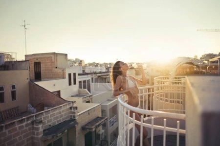 Girl in bikini drinking on a balcony