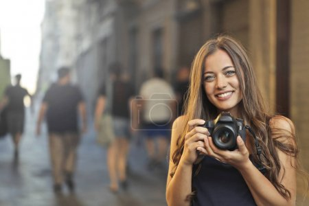 Girl with a camera in a downtown road