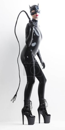 Photo pour Femme debout, portant des vêtements de latex avec un fouet - image libre de droit
