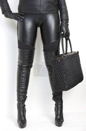 Photo pour Bottes noires à la mode avec un sac à main - image libre de droit