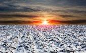sunset landscape over winter plouged farm field