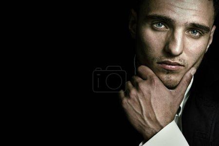 Photo pour Beau portrait de visage d'homme avec des yeux bleus sexy sur fond noir foncé - image libre de droit