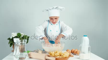 Young baker playing with dough and laughing at camera isolated on white