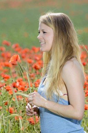 Photo pour Joyeux jeune femme blonde dans le champ de pavot - image libre de droit