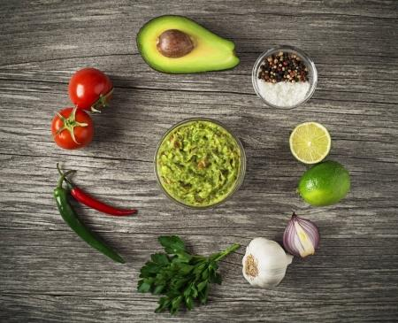 Photo for Avocado guacamole with fresh ingredients on wooden table - Royalty Free Image