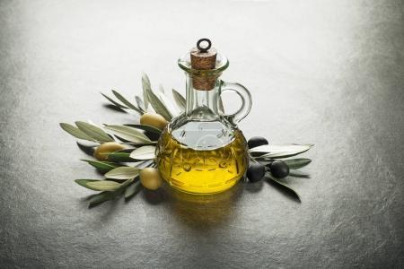 Photo pour Huile d'olive et le rameau d'olivier sur la table grise - image libre de droit
