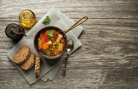 Photo pour Soupe de pâtes aux légumes et herbes sur fond en bois - image libre de droit