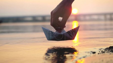 Mans hand putting paper boat on the water during beautiful sunset with reflection sun in the sea