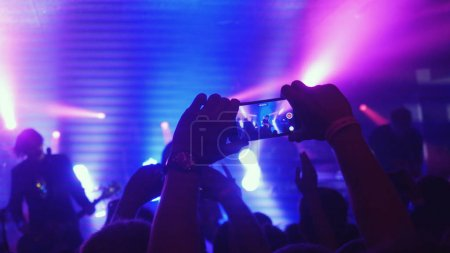 Fans waving their hands recording video and taking pictures with smart phones at music concert. People crowd partying at rock concert in night club.