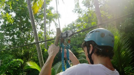 Tourist man in helmet slides a rope descent in tropical jungle.