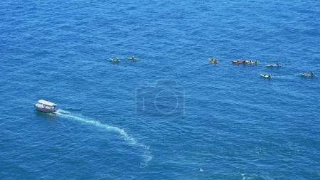 Boat and kayaks floating in blue sea