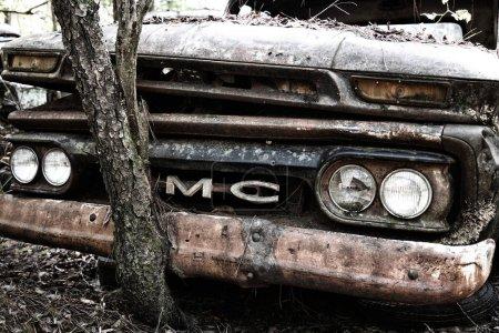 Photo pour White, Ga / Usa - 27 octobre 2018 - Gros plan d'un vieux camion Gmc de rebut dans une cour à ferraille où pousse un arbre sur le grill avant - image libre de droit