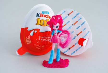 Kinder Joy eggs with doll on gray background