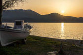 Sunset seascape with old boat on embankment of Thassos town, East Macedonia and Thrace