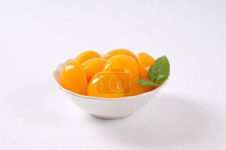 Photo for Bowl of peeled and halved peaches on white background - Royalty Free Image