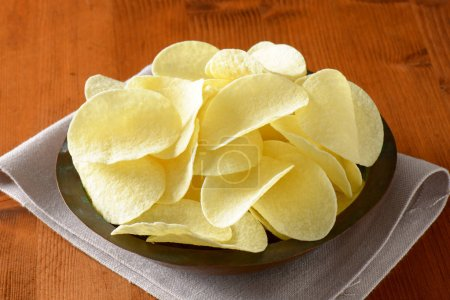 Photo for Bowl of thin salted potato chips (crisps) - Royalty Free Image