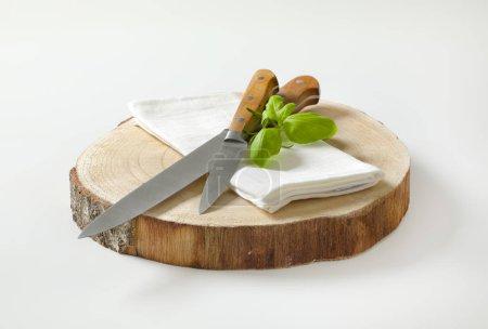 Photo pour Ensemble de deux couteaux de cuisine pointus pointus et une serviette blanche sur dalle de bois ronde - image libre de droit