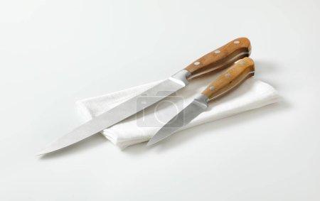 Photo pour Couteau utilitaire de cuisine et couteau à tartiner sur serviette blanche - image libre de droit