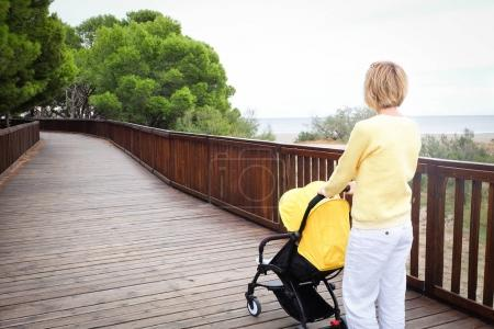 Blond hair woman strolling a baby in carriage