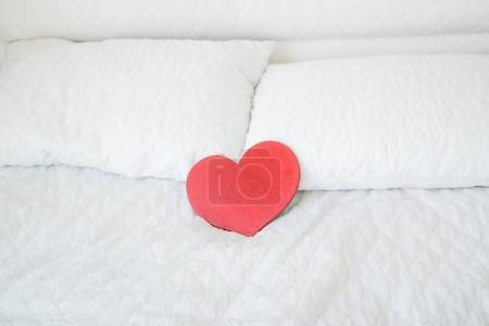 Red wooden heart symbol on white bed