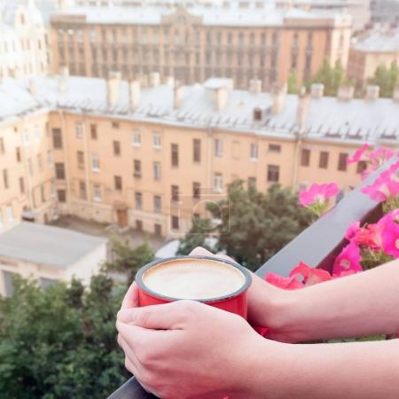 Woman drinking coffee on balcony